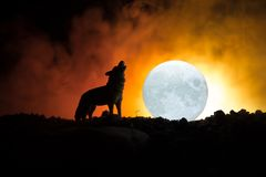 Silhouette of howling wolf against dark toned foggy background and full moon or Wolf in silhouette howling to the full moon. Hallo. Ween horror concept Stock Photography