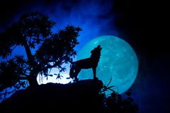 Silhouette of howling wolf against dark toned foggy background and full moon or Wolf in silhouette howling to the full moon. Hallo. Ween horror concept Royalty Free Stock Photo