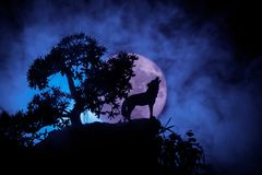 Silhouette of howling wolf against dark toned foggy background and full moon or Wolf in silhouette howling to the full moon. Hallo stock image