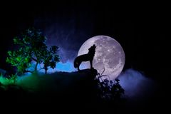 Silhouette of howling wolf against dark toned foggy background and full moon or Wolf in silhouette howling to the full moon. Hallo. Ween horror concept Royalty Free Stock Photography