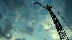 Silhouette of huge building crane against cloudy evening sky, view from bottom. Stock footage stock footage