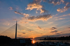 Silhouette of a huge cable bridge over Sava river at sunset in Belgrade royalty free stock image