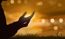 Silhouette of human hand with open palm praying to god. At sunset background royalty free stock images