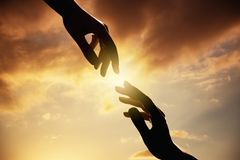 Silhouette of human hands on sunset.Trust and help concept. royalty free stock images