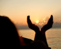 Silhouette human open empty hands with palms up over sun Royalty Free Stock Photography