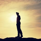 Silhouette human standing on rocky pedestal on nature daybreak  background. Royalty Free Stock Photography