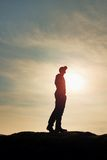 Silhouette human standing on rocky pedestal on nature daybreak  background. Stock Images