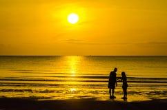 Silhouette. Human walk on the beach in twilight time Stock Photo