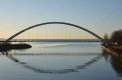 Silhouette of the Humber Bay Arch Bridge. The curving silhouette of the Humber Bay Arch Bridge is mirrored in the smooth waters of the river below Stock Photo