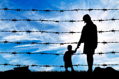 Silhouette of hungry refugees mother and child. Concept of refugee. Silhouette of hungry refugees mother and child near the fence of barbed wire Stock Images