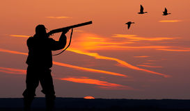 The silhouette of a hunter on sunset background. Silhouette of man on the hunting Royalty Free Stock Images