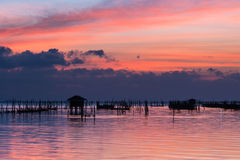 Silhouette of hut over the water at sunset Royalty Free Stock Photo