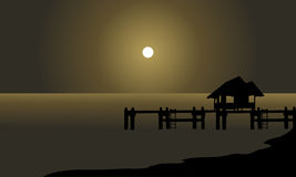 Silhouette of hut and pier Stock Photos