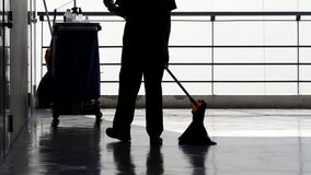 Silhouette of cleaning service people sweeping floor. Silhouette image of cleaning service people sweeping floor with mop and other equipment on trolley Royalty Free Stock Photo