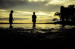 Silhouette image concept young boy standing at the beach Stock Image