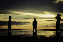 Silhouette image concept young kids playing at the sandy beach Royalty Free Stock Photo