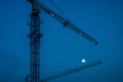 The silhouette image of the construction tower canes at dusk wit Royalty Free Stock Photo