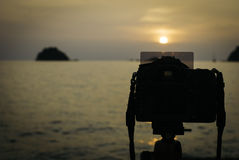 Silhouette image of digital camera on tripod during sunset Royalty Free Stock Photo