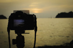 Silhouette image of digital camera on tripod during sunset Stock Image