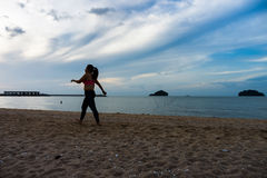 The silhouette image of fat Asian woman is walking on the beach Stock Image