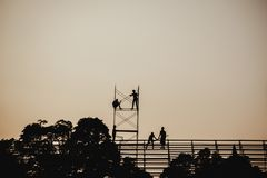 Silhouette image of a group of workers working on scaffolding for construction royalty free stock images