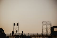 Silhouette image of a group of workers working on scaffolding for construction stock photos