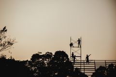 Silhouette image of a group of workers working on scaffolding for construction royalty free stock photos