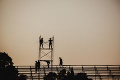 Silhouette image of a group of workers working on scaffolding for construction. In the evening royalty free stock image