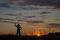 Silhouette image of a lady standing and waving good bye to setting sun Royalty Free Stock Photo