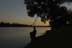 Silhouette image of man sitting on tree trunk beside the lake Stock Photos