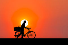 Silhouette image. A man walking with bicycle. Royalty Free Stock Photo