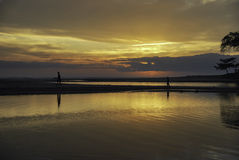 Silhouette image of two boys walking inline at the shore with beautiful sunrise sunset background Royalty Free Stock Photos