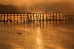 Silhouette image of wooden bridge and sailing boat during sunris Royalty Free Stock Photography