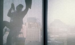 Silhouette images of man cleaning the window office building royalty free stock image