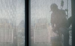 Silhouette images of man cleaning the window office building royalty free stock photo