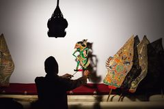 Silhouette of indonesian puppeteer with old javanese shadow puppets royalty free stock images
