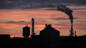 Silhouette of industrial building with smoking chimney stock footage