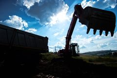Silhouette of industrial excavator loading earth Stock Photo