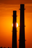 Silhouette of industrial factory at gold sunset Stock Images
