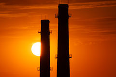 Silhouette of industrial factory at gold sunset Royalty Free Stock Images
