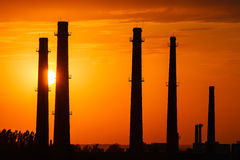 Silhouette of industrial factory at golden sunset Royalty Free Stock Photo