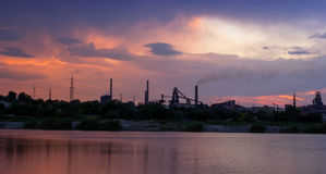 Silhouette of industrial factory at sunset mirror in water Stock Photo