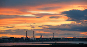Silhouette of industrial factory at sunset mirror in water Stock Photography