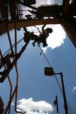 Silhouette industrial hanging working at height wearing helmet using face shield safety equipment protection stock images