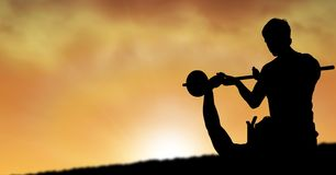 Silhouette of instructor assisting man in lifting barbells during sunset. Digital composite of Silhouette of instructor assisting men in lifting barbells during Stock Photo