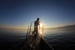 Silhouette of intha fisherman against the sunset sky Stock Photos