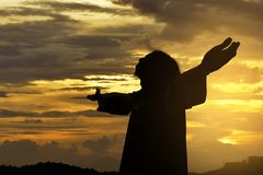 Silhouette of Jesus christ standing with raised arms. At sunset background stock photos