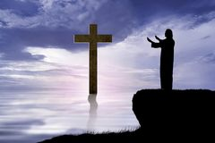 Silhouette of Jesus raising hand and praying. On the hill Royalty Free Stock Photos