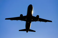 Silhouette of jet aircraft against blue sky. Royalty Free Stock Images