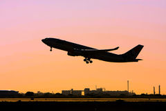 Silhouette of jet airliner in flight Stock Photos